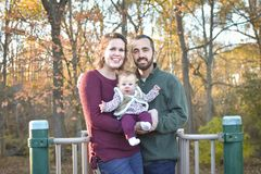 Family of Three at the Park in the Fall. A family of three at the Park in the fall. A mother wearing a plum colored sweater and blue jeans. Dad is wearing a Stock Photos