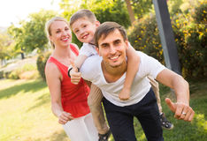 Family of three in park in summer day. Cheerful young family of three looking happy and holding thumbs up in park on summer day stock photos