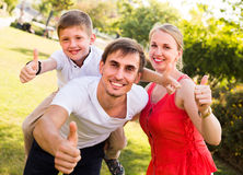 Family of three in park in summer day. Positive young family of three having fun in park on summer day and holding thumbs up Royalty Free Stock Photography