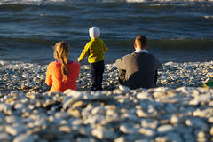 Family of three on pebble beach Stock Image
