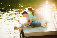 Family of three people having fun at riverside on sunset time. Father, mother and little baby girl siting together near water with sun light reflection in it Stock Image