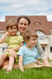 Family of three people on lawn in front of house Stock Images