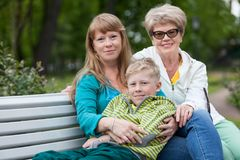 Family of three people looking at camera sitting on garden bench together in hug, young boy, adult and elderly women Stock Image
