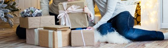 Family of three people, mom, dad and daughter, sitting on the floor, around the gifts, the girl holds a single big box, next to it royalty free stock photos
