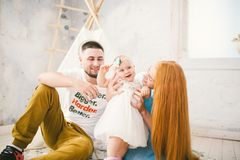 A happy family of three. Mom, dad, child one year old girl in dress play, laugh, smile in bright room. Sunny weather Royalty Free Stock Photography