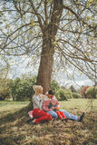 Family of three people resting under a tree Royalty Free Stock Images