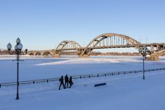 Family of three people walking along a snow-covered town royalty free stock photography