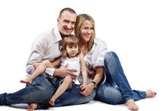 Family of three persons sits on a floor Stock Images