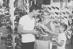 Family of three picking sport shoes in store Royalty Free Stock Photos