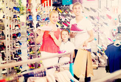 Family of three picking sport shoes in store Royalty Free Stock Image