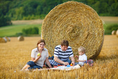 Family of three picnicking on yellow hay field in summer. Royalty Free Stock Image
