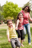 Family of three play in the park Stock Photography