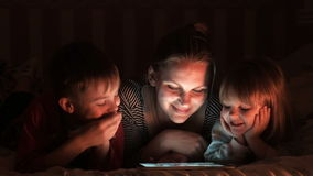 Family of three playing on pad. Mother and two kids lying on bed while playing on tablet stock footage