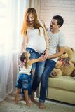 Family of three. Pregnant mom, dad and little daughter. Stock Photos