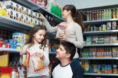 Family of three purchasing food for week Stock Photos