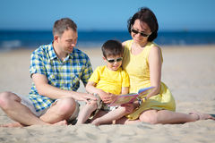 Family of three reading book on beach Royalty Free Stock Image