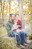 Family of Three by the River in the Fall. A family of three in the forest in the fall.  A mother wearing a plum colored sweater and blue jeans.  Dad is wearing a Stock Images