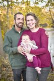 Family of Three by the River in the Fall. A family of three in the forest in the fall.  A mother wearing a plum colored sweater and blue jeans.  Dad is wearing a Stock Image