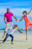 Family of three running along the tropical beach, laughing and enjoing time together. Stock Image