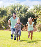Family of three running on grass Royalty Free Stock Image