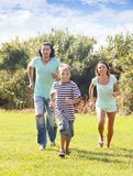 Family of three running   at  park Stock Photos
