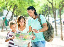 Family of three searching way at  map Stock Image