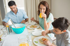 Family of three sitting at dining table Stock Photography