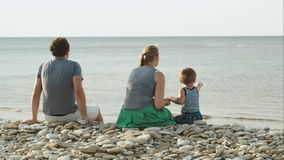 Family of three sitting on pebble beach by the stock video footage