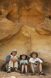 Family of three sitting in rock shelter Stock Photography