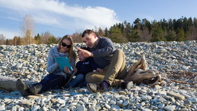 Family of three sitting on the stony shore and Royalty Free Stock Photography