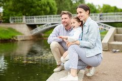 Chill by waterside. Family of three sitting by waterside in park and looking at birds while enjoying their chill royalty free stock photos