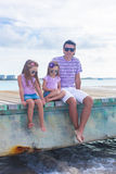Family of three sitting on wooden dock enjoying Stock Photos
