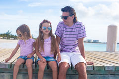 Family of three sitting on wooden dock enjoying Royalty Free Stock Images
