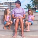 Family of three sitting on wooden dock enjoying Stock Photo