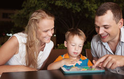 Family of three spending time in cafe with tablet Stock Image