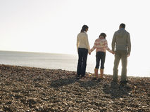 Family Of Three Standing On Beach Stock Photos