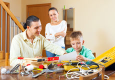 Family of three with teenage boy doing something with the workin Royalty Free Stock Image
