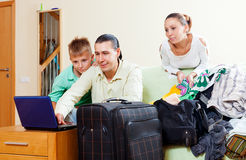 Family of three with teenager reserving tickets and choosing clo. Thes for vacation in the living room Stock Photos