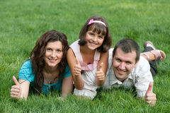 Family of three with thumbs up in the park Stock Photo