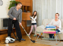 Family of three tidying up a room Royalty Free Stock Images