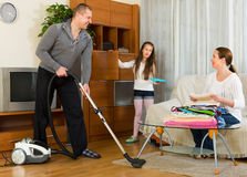 Family of three tidying up a room Stock Photos