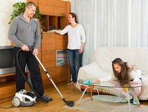Family of three tidying up a room Royalty Free Stock Image