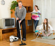 Family of three tidying up a room Stock Images