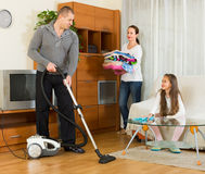 Family of three tidying up a room Royalty Free Stock Photography