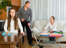 Family of three tidying up a room Stock Photography