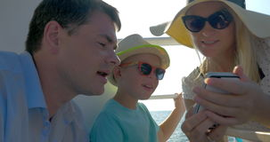 Family of three traveling by sea and using mobile. Happy family of three traveling by ship on sunny day. Mother, son and father watching photos on mobile, then stock footage