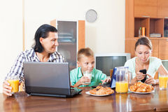 Family of three using electronic devices during breakfast Stock Photo