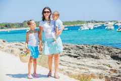 Family of three walking along tropical beach Royalty Free Stock Photos