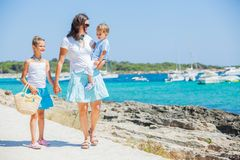 Family of three walking along tropical beach Royalty Free Stock Photography