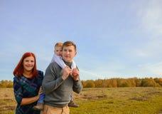 Family of three walking outdoors Stock Photography